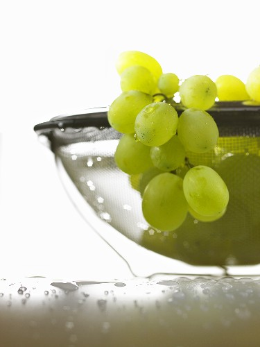 Green grapes with drops of water in sieve