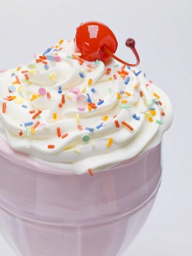 Milkshake with cream, sprinkles & cocktail cherry (close-up)