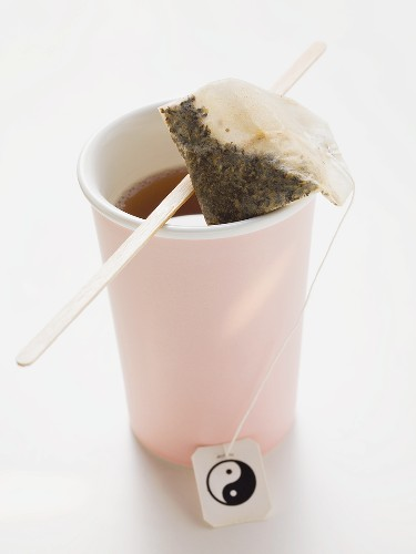 Tea in pink plastic cup with tea bag