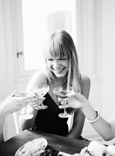 Young woman making a toast with an aperitif