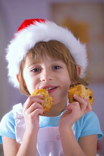 Little girl in Santa hat eating raisin biscuits