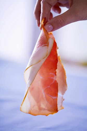 Woman holding a slice of raw ham in her hand