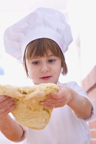 Girl in chef's hat handling pastry