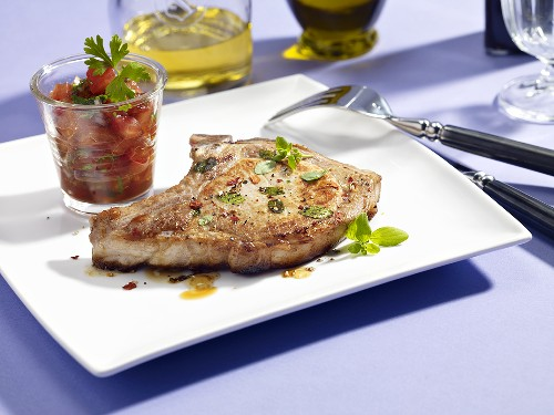 A pork chop with a glass of tomato salsa