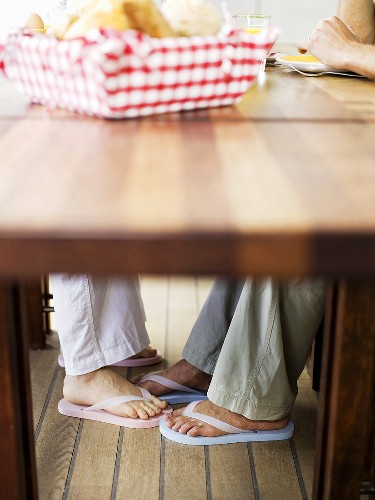 Couple touching feet under table