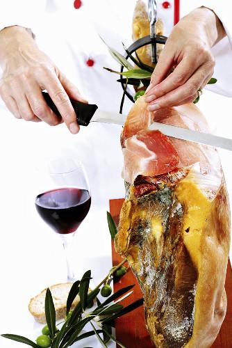 Chef cutting Serrano ham, close-up, mid section