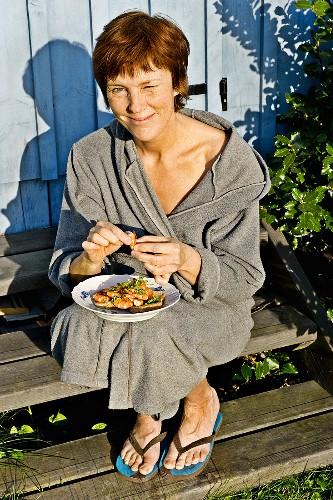 Woman in bathrobe holding plate of prawns