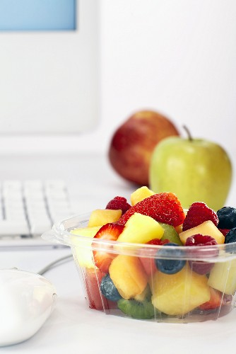 Bowl of fruit salad beside computer on office desk