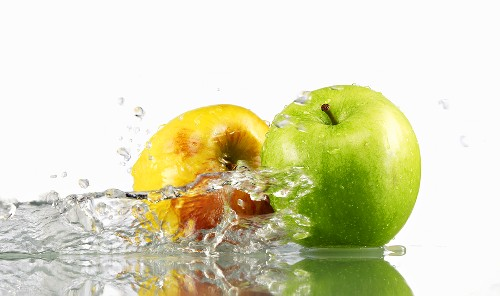 One green and one yellow apple with splashing water