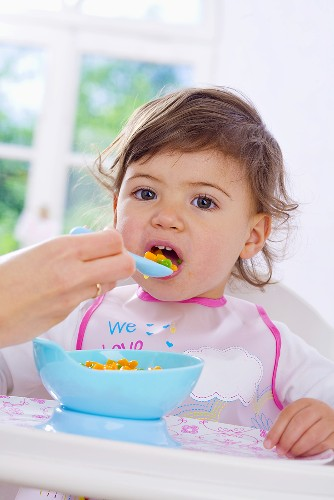 Small child being fed vegetables