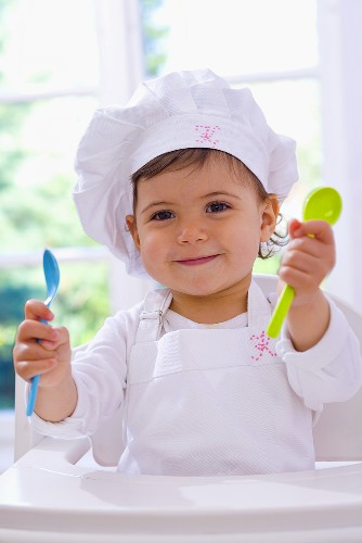 Little girl in chef's hat holding plastic spoons