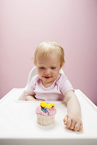 A baby with a cupcake