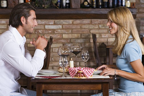 A couple sitting at a table in a wine bar