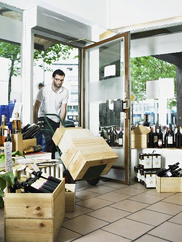 A man pushing a trolley of wine crates into a wine shop