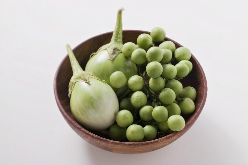 Green baby aubergines in wooden bowl