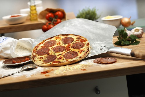 Salami pizza with pizza paddle