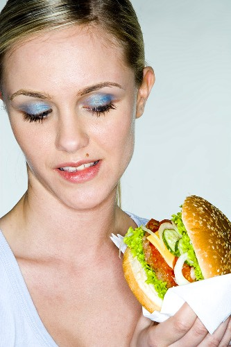 Young woman holding a hamburger in her hand
