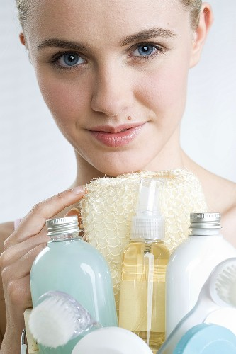 Young woman with assorted cosmetics