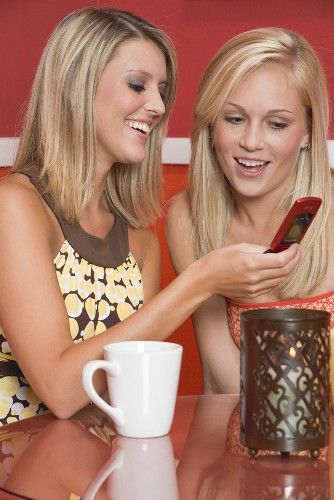 Two blond girls in café looking at mobile phone