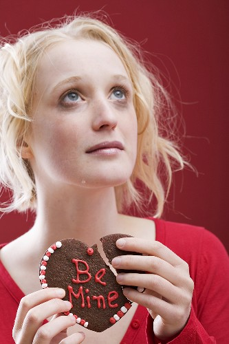Sad young woman with a broken chocolate heart