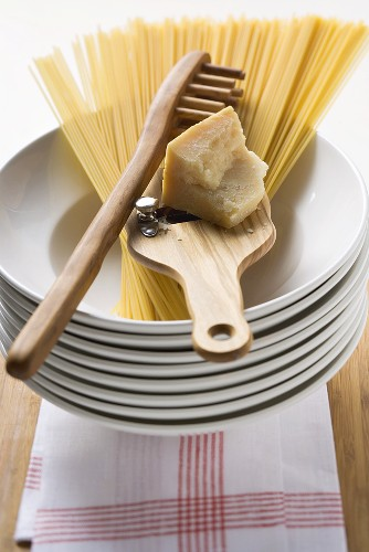 Spaghetti with spaghetti server & Parmesan on pile of plates