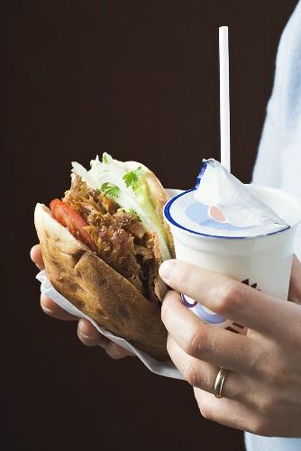 Hands holding döner kebab and ayran