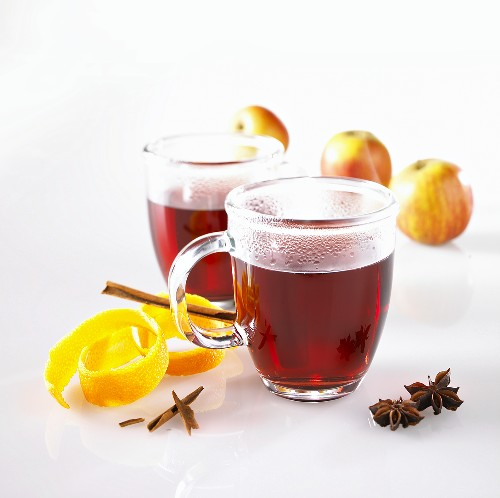 Mulled wine in glass mugs, orange peel, spices and apples