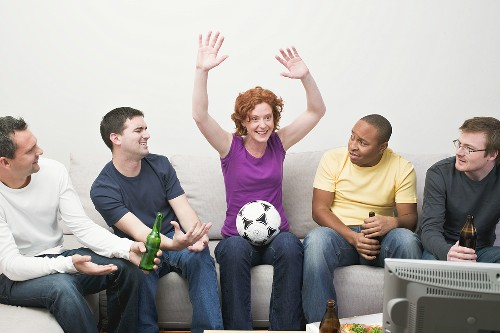 Friends with football and beer sitting in front of TV