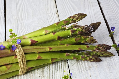 A bundle of green asparagus on white wood