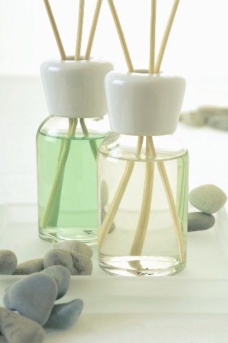 Two bottles of fragrance with aroma sticks