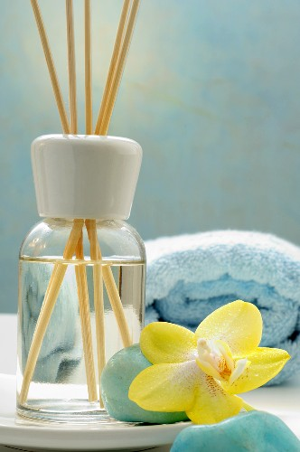 Bottle of fragrance with aroma sticks and orchid