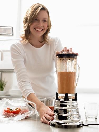 Woman making tomato juice in liquidiser