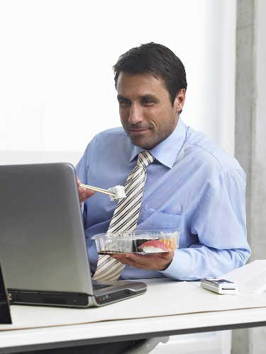 Businessman eating sushi while looking at his laptop