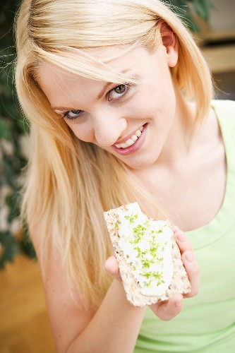 Young woman eating crispbread with quark and cress