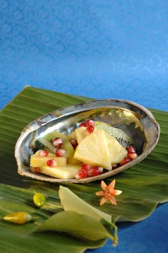 Pineapple, kiwi fruit & pomegranate seeds in abalone shell