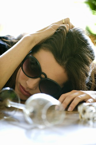 Woman with hangover, head on table, with empty wine glasses