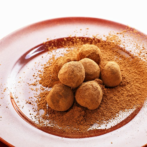 Chocolate Truffles in a Pile of Cocoa Powder on a Plate