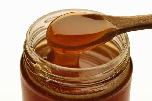 Manuka honey running into jar from wooden spoon
