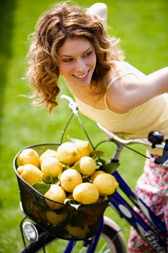 Woman with basket full on lemons on bicycle