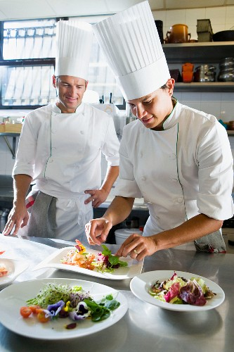 Chefs in a commercial kitchen preparing a salad