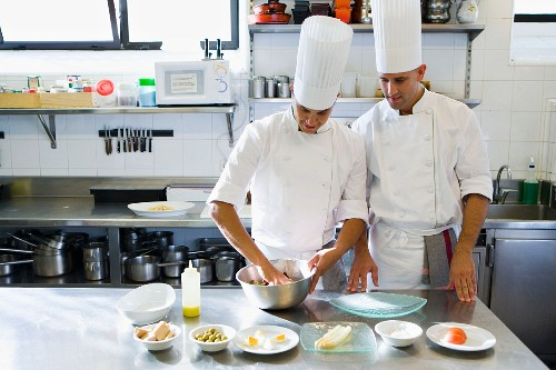 Two chefs in a commercial kitchen arranging food on a plate