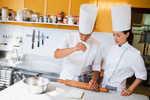 A head chef and trainee chef preparing dough