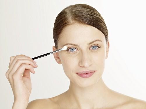 Woman putting on eye shadow