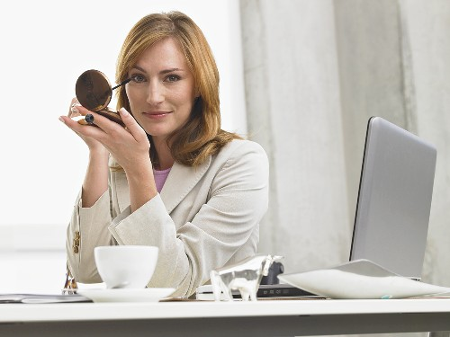 Businesswoman putting on eye make-up at her desk