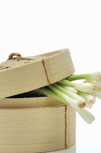Spring onions in bamboo steamer