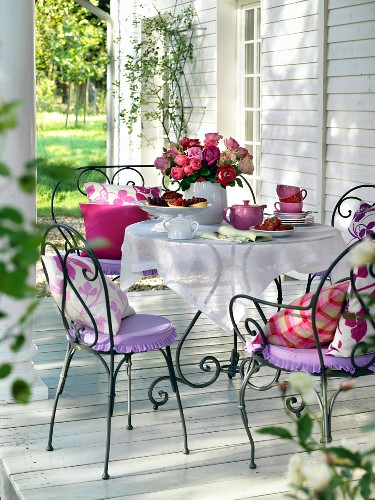 Iron chairs around a table decorated with a bunch of roses for afternoon coffee on the terrace
