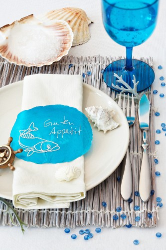 A maritime place setting with a blue stemmed glass on a raffia placemat