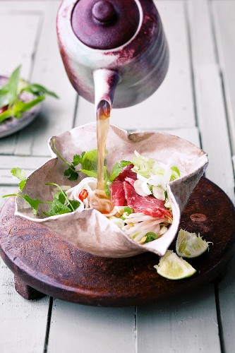 Broth being poured over ingredients for Vietnamese beef soup
