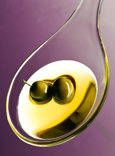 Olive oil on plastic spoon; green olives