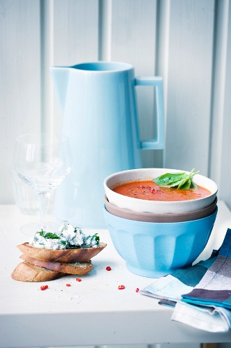 Spicy tomato soup with grilled bread in a soup bowl served with bread and cream cheese